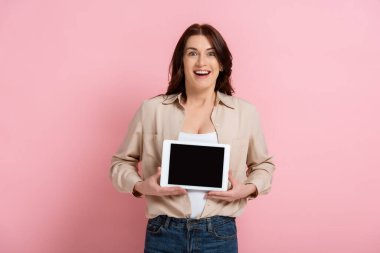Cheerful woman holding digital tablet with blank screen and looking at camera on pink background stock vector