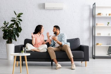 Positive couple smiling at each other while sitting on sofa under air conditioner at home stock vector