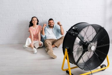 Young couple smiling at camera and showing yeah gesture while sitting on floor near electric fan stock vector