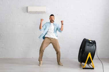 Positive man showing yes gesture while standing near air conditioner and electric fan in living room stock vector