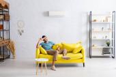 Pozitív férfi kezében távirányító légkondicionáló és mosolyog a kamera kanapén otthon