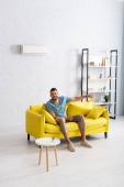 Pozitivní muž ukazuje prstem a dívá se na kameru doma na gauči