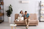 Selektiver Fokus eines jungen Paares, das auf der Couch im Wohnzimmer in die Kamera blickt