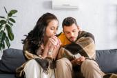 In Plaid gehüllte Frau sitzt neben Freund und hält Fernbedienung der Klimaanlage auf Couch