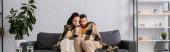 Panorama-Ernte von Paar in karierte Halterung Fernbedienung der Klimaanlage auf dem Sofa eingewickelt