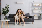 Mladý pár zabalený v kostkovaném držení dálkového ovládání klimatizace v obývacím pokoji