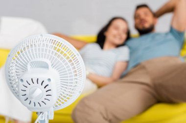 Selective focus of electric fan near young couple sitting on sofa