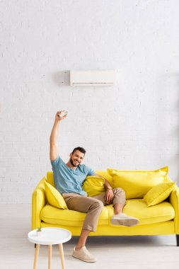 Cheerful man smiling at camera while holding remote controller of air conditioner in living room stock vector