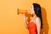 Photo profile of young woman in swimsuit screaming in megaphone on orange