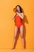 Photo young woman in swimwear holding megaphone and screaming on orange