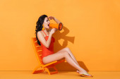 Photo attractive woman in swimwear holding megaphone and screaming while sitting on deck chair on orange