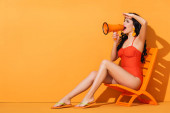 Photo attractive girl in swimwear holding megaphone and screaming while sitting on deck chair on orange