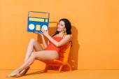 veselá mladá žena v plavkách drží papír boombox, zatímco sedí na palubě židle na oranžové