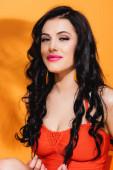 pozitivní mladá žena v plavkách při pohledu na kameru na oranžové