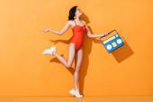 šťastná žena v teniskách, slunečních brýlích a plavkách s papírovým výstřihem boombox na oranžové