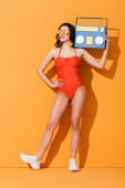 šťastná žena v teniskách, slunečních brýlích a plavkách drží papír střih boombox, zatímco stojí s rukou na boku na oranžové