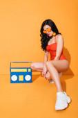 stylová žena v teniskách, plavkách a slunečních brýlích sedící u papírové krabičky na oranžové