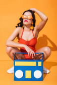 Photo stylish girl in sneakers, bathing suit and sunglasses sitting near paper cut boombox and touching hair on orange