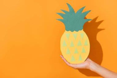 Cropped view of woman holding paper cut pineapple on orange stock vector