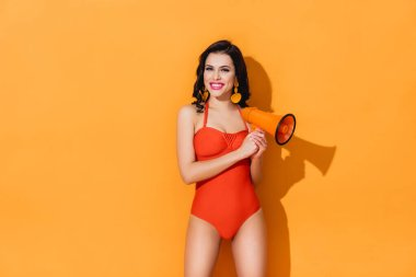 Happy young woman in swimsuit standing and holding megaphone on orange stock vector