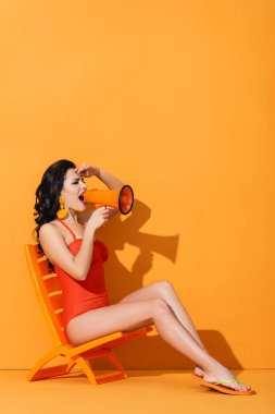 Young woman in swimwear holding megaphone and screaming while sitting on deck chair on orange stock vector