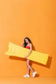 glückliche Frau in Badeanzug und Turnschuhen mit aufblasbarer Matratze und anrührenden Haaren auf orange