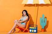 boldog fiatal nő fürdőruhában ül a fedélzeten szék közelében papír boombox, kaktusz és esernyő a narancs
