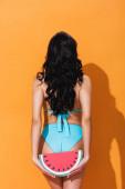 zadní pohled na ženu v plavkách stojící a držící papírový meloun na oranžové