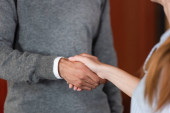 Photo cropped view of businessman and businesswoman shaking hands