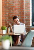selektivní zaměření vzrušené podnikatelky pomocí notebooku v moderní kanceláři