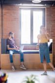 Selektiver Fokus der glücklichen Geschäftsfrau, die mit dem Smartphone spricht und Pappbecher in der Nähe des Geschäftsmannes mit dem Laptop hält