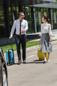 Selective focus of smiling business people walking with suitcases on urban street