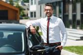 Selektiver Fokus des Geschäftsmannes mit der Hand in der Tasche, der in die Kamera neben dem Auto auf der Stadtstraße lächelt