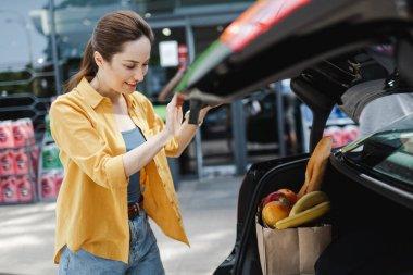 Gülümseyen kadının seçici odak noktası, alışveriş çantasının yanında duran, araba bagajında yiyecek olan şehir caddesi.