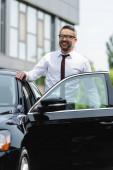 Selektiver Fokus eines lächelnden erfolgreichen Geschäftsmannes, der in der Nähe eines Autos auf einer städtischen Straße in die Kamera lächelt