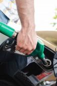 Oříznutý pohled na muže držícího palivovou trysku poblíž otevřeného krytu nádrže venku