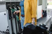 Oříznutý pohled na ženu při tankování trysky v blízkosti auta na čerpací stanici na městské ulici
