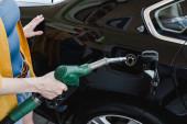 Beschnittene Sicht auf Frau, die Auto an Tankstelle betankt