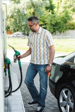 Selective focus of man holding fueling nozzle on gas station near auto on urban street stock vector