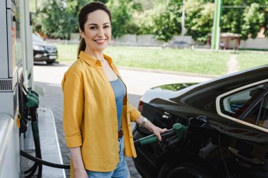 Selective focus of woman smiling at camera while refueling car on gas station stock vector