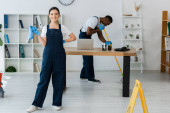 Selektivní zaměření usměvavější čistič drží hadr v blízkosti afroamerické kolegyně mytí podlahy v kanceláři