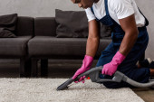Cropped view of african american cleaner using vacuum cleaner on carpet in living room