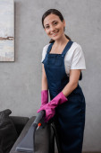 Smiling cleaner in rubber gloves holding vacuum cleaner near couch at home