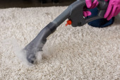 Cropped view of cleaner holding brush of vacuum cleaner with hot steam near carpet