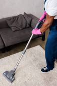 Cropped view of african american cleaner in uniform using vacuum cleaner at home