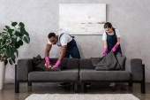 Multikulturális tisztítószerek egyenruhás takarító kanapéban ronggyal a nappaliban