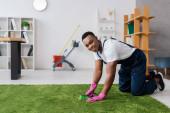 Lächelnde afrikanisch-amerikanische Putzfrau mit Bürste beim Teppichputzen im Büro