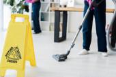 Oříznutý pohled na uklízeče pracující v kanceláři poblíž mokré podlahové cedule s nápisem na podlaze