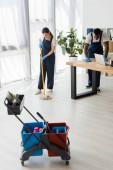 Selektivní zaměření multiethnic čističů praní podlahy a stolu při práci v kanceláři