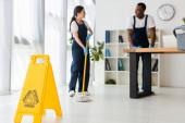 Selektivní zaměření značky mokré podlahy a usměvavé multietnické čističe pracující v kanceláři